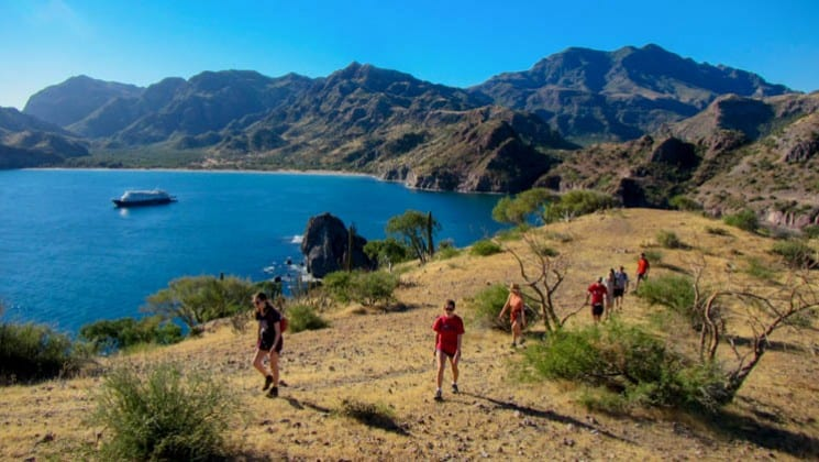 hikers along cliff with baja's bounty small ship in bay below