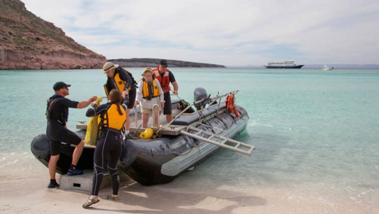 skiff landing on beach with baja's bounty small ship cruise in bay