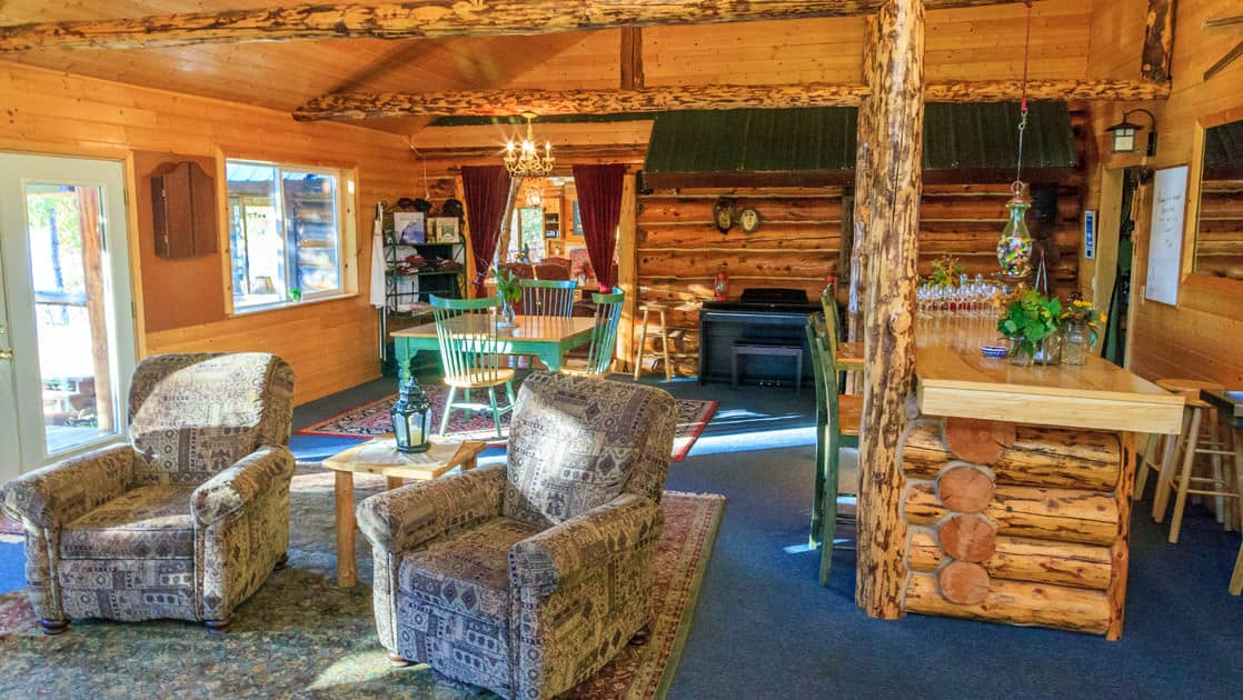 The bar at Winterlake Lodge with comfortable chairs, a wood stove, and large windows is a place to relax after a day of adventure in the Alaskan wilderness