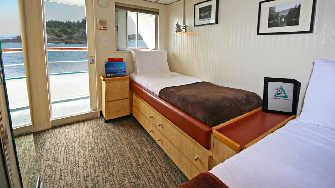 Category AA stateroom aboard Baranof Dream with two single beds, window, and doorway.