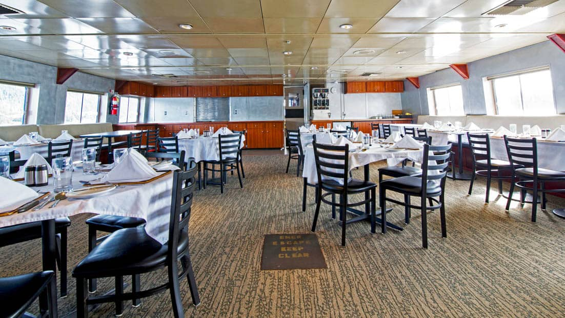 Dining room with set tables aboard Baranof Dream.
