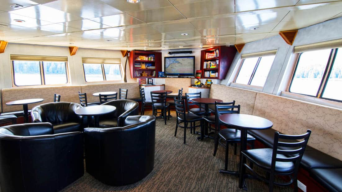 Lounge are with chairds, tables, tv, and windows aboard Baranof Dream.