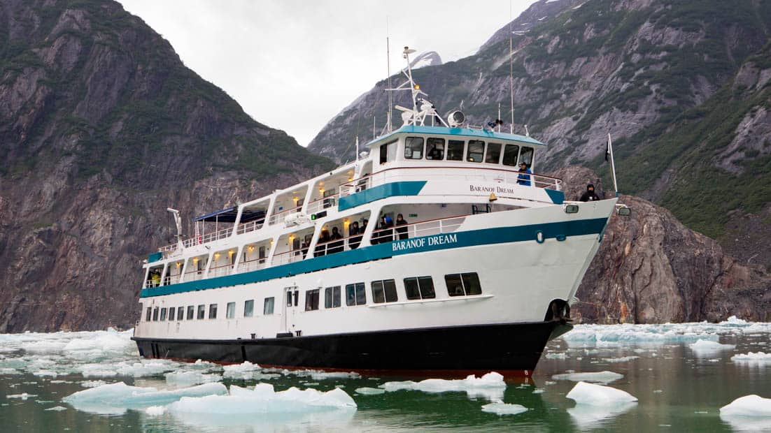 Bow of Baranof Dream cruising in Alaskan fjords with ice around.