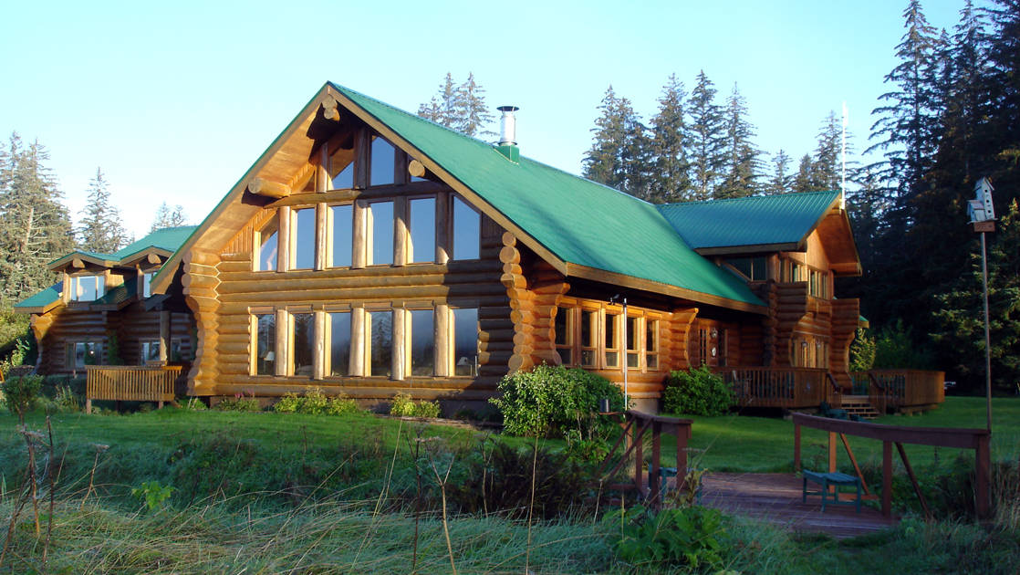 Large windows at the Bear Track Inn face large growth forest, open meadows, and views of Icy Strait in Alaska
