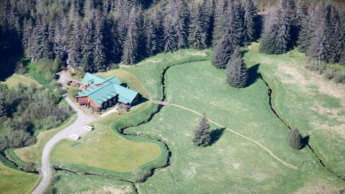 An aerial view of the Bear Track Inn, surrounded by large growth forests and open meadows in Alaska