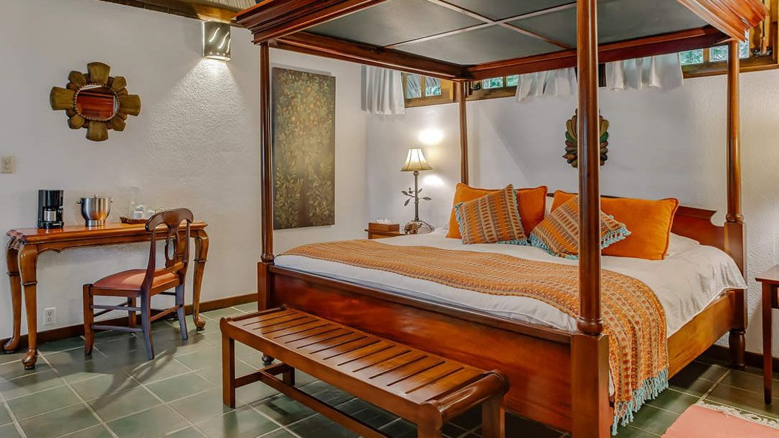 King sized canopy bed with wood detailing and small writing desk in garden suite bedroom at Chaa Creek Lodge in Belize.