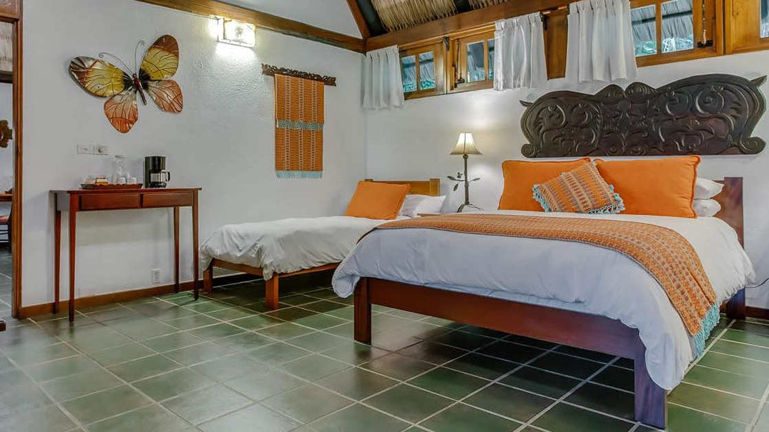 Large bed and nearby daybed with tapestries and local woodworking decorating the walls of a garden suite at Chaa Creek Lodge in Belize