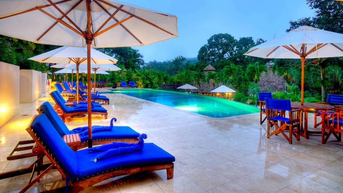 Shaded lounge chairs and intimate tables next to the infinity swimming pool at Chaa Creek Jungle Lodge in Belize