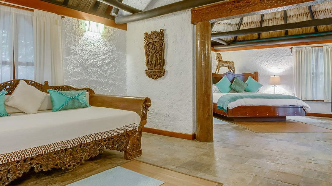 Wood daybed in living room with master bedroom visible in the Macal River Suite at Chaa Creek Lodge in Belize.