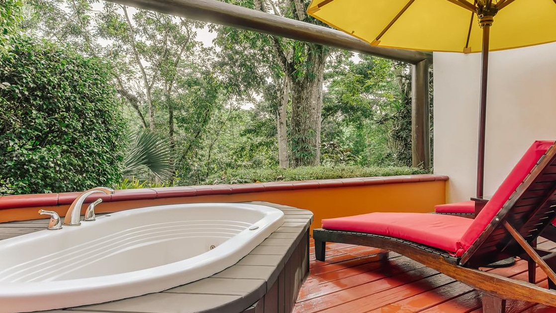Private outdoor Jacuzzi with shaded lounging area and rainforest views at the Lodge at Chaa Creek in Belize.