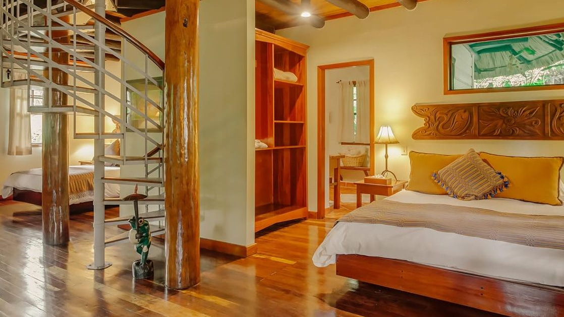 Two bedrooms with wraparound staircase leading to upper-level living area in a villa at Chaa Creek Jungle Lodge in Belize.