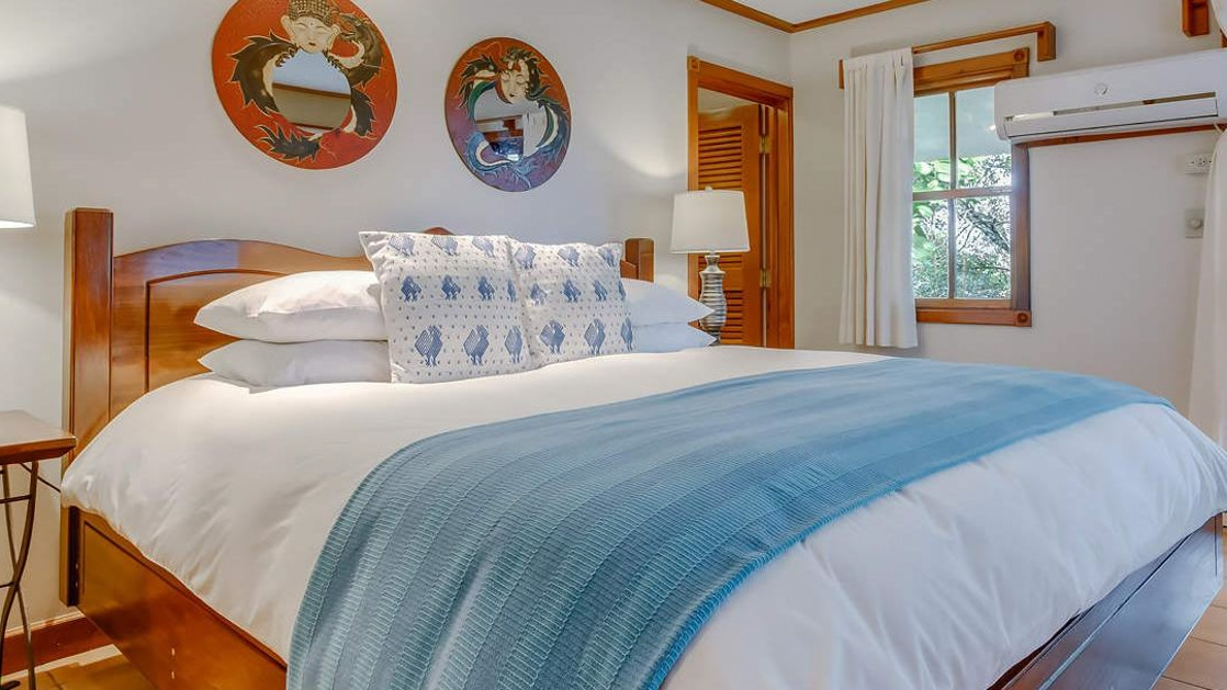 King bed with fresh blue decor and local wood artwork in the spa villa master bedroom at the Lodge at Chaa Creek in Belize.