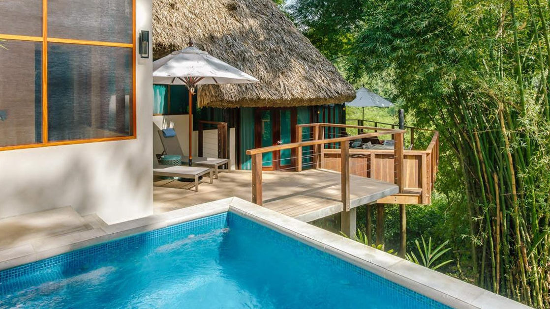 Infinity pool and two outdoor decks on the Tree Top Villa at Chaa Creek with surrounded by jungle foliage.