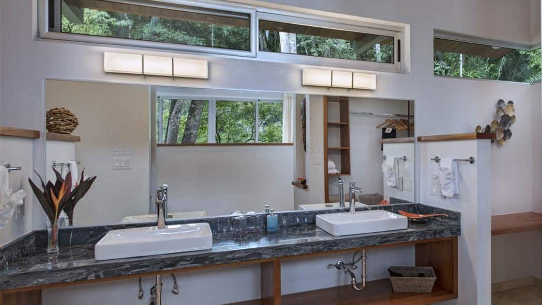Large bathroom with two sinks and huge mirror, bathed in natural light from large windows at Chaa Creek Jungle Lodge in Belize