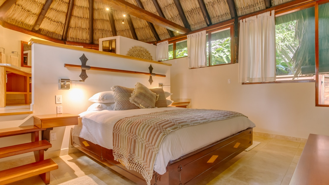 Large bed surrounded by windows looking into the jungle with a thatched roof overhead in the Tree Top Villa at Chaa Creek in Belize.