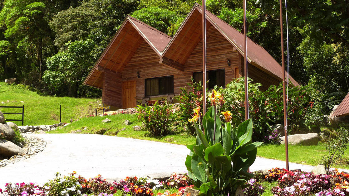 A picutre of the two pitched Boquete Tree Mountain Resort with flowers in the front.