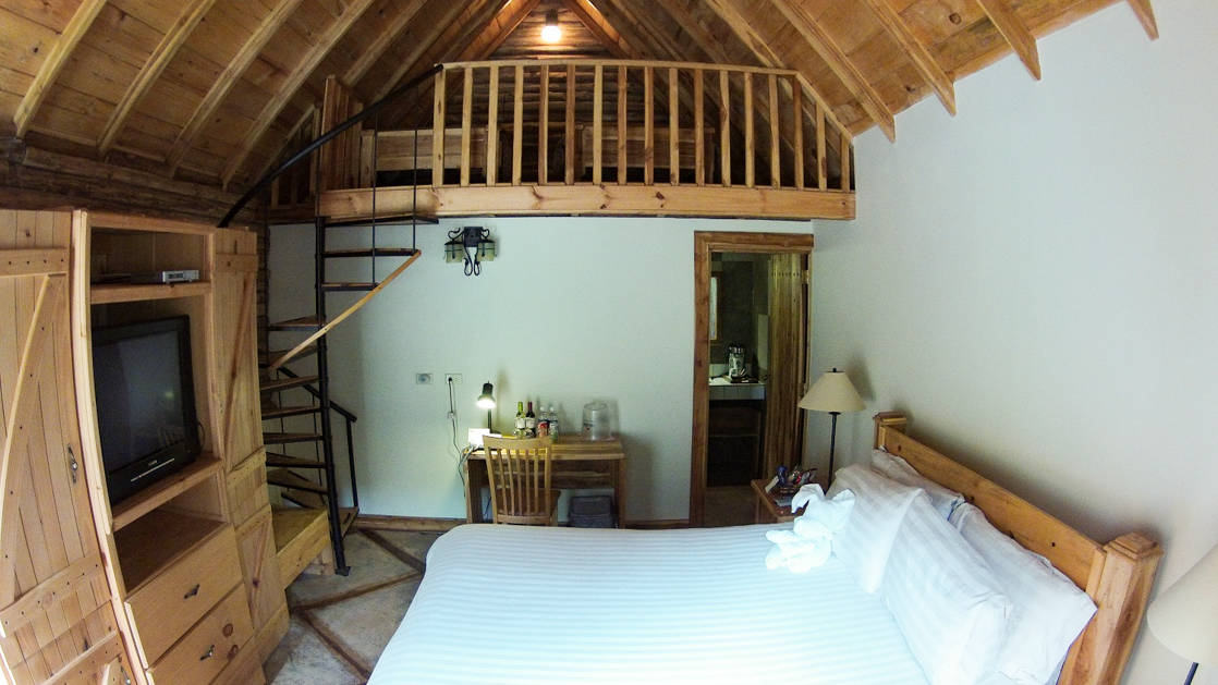 A room at Boquete Tree Trek Mountain Resort with a loft, queen bed and desk.