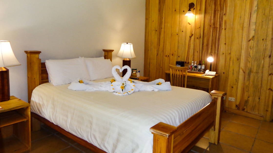 A queen bed in a room at Boquete Tree Trek Mountain Resort.