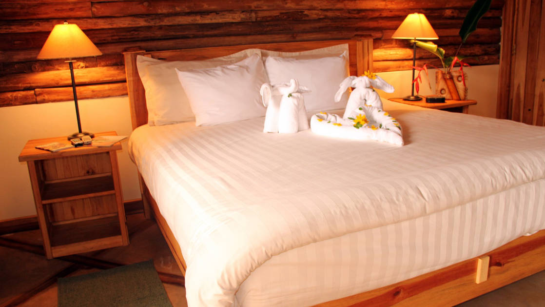 A room at Boquete Tree Trek resort with a large queen bed with whit linens.