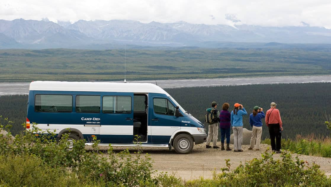 Guests stand outside the van in front of a scenic vista with snowy mountains in Alaska, on the way to Camp Denali, to discuss geology, ecology and the history of the National Park.