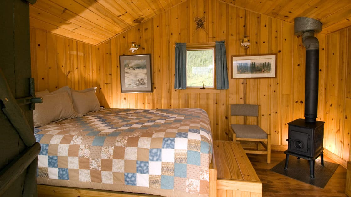 A queen-sized bed and a wood stove keep guests cozy and warm while staying at Camp Denali, a wilderness lodge with historic ties to the preservation of the national park in Alaska.