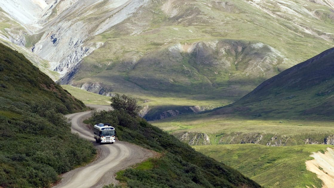 A bus drives on a winding dirt road along a mountain with a green valley and snow-capped peaks in the distance, en route between the national park depot and Camp Denali in Alaska.