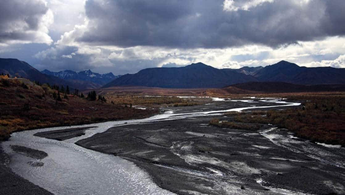 A big river meanders through the wide-open Alaskan wilderness under mountains and a stormy sky near Camp Denali, a wilderness lodge with historic ties to the national park