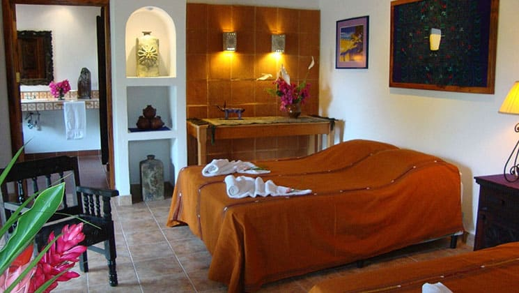 room in the candelaria lodge in guatemala with two beds, pictures on the wall and a doorway leading to another room