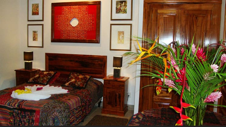 room in the candelaria lodge in guatemala with a large bed, flowering plant and pictures on the wall