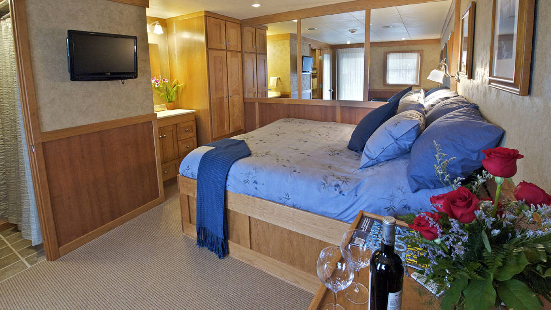 jr commodore suite aboard the Safari Explorer Hawaii small ship with large blue bed, flat screen tv and windows behind it