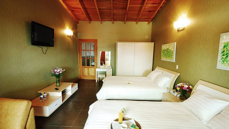 room at casa grande bambito with two beds, green walls and a door leading to another area
