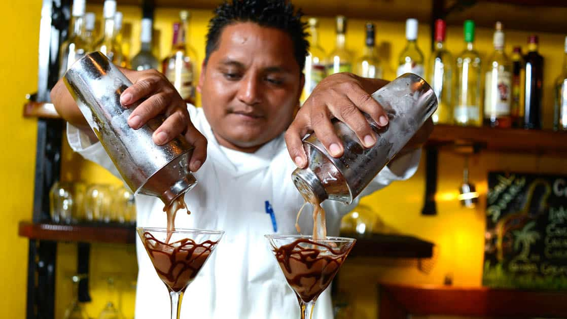 Bartender pouring two drinks into martini glasses at the main bar at Chaa Creek Jungle Lodge in Belize