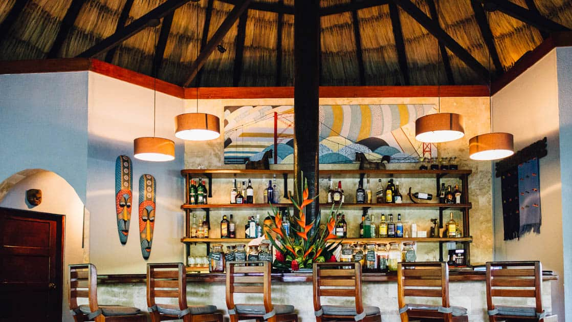 Six seats at the main bar with top-shelf liquor and a relaxing vibe thanks to the thatched roof, at Chaa Creek Jungle Lodge in Belize