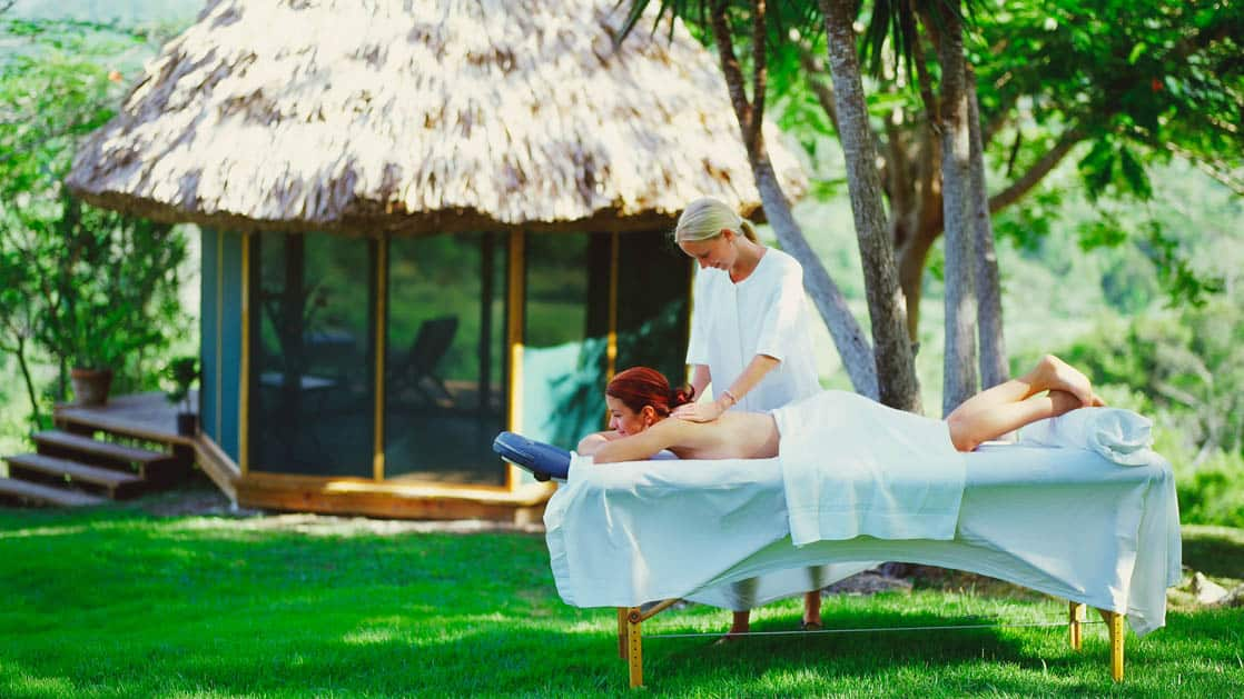 Woman receives outdoor massage treatment near thatched roof gazebo at Chaa Creek Jungle Lodge in Belize