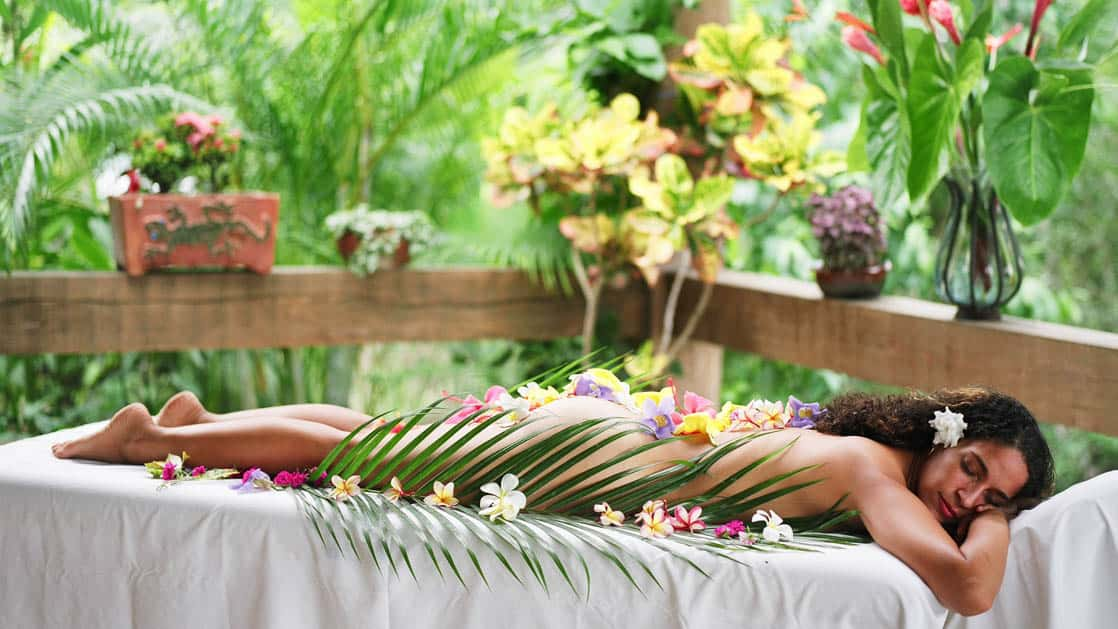 Relaxed woman covered in flower petals receiving spa treatment at Chaa Creek Jungle Lodge in Belize
