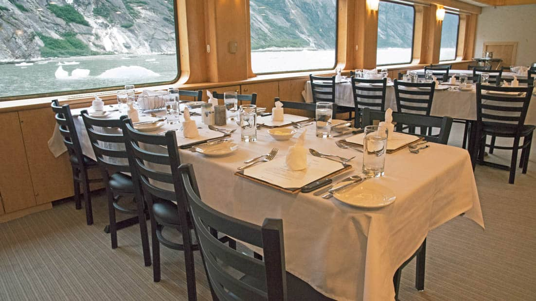 Dining room with several tables by the windows aboard Chichagof Dream