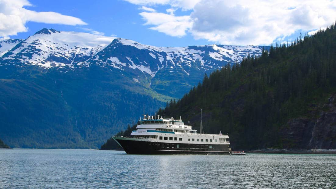 Small ship Chichagof Dream cruising past snowy mountain ranges in alaska.