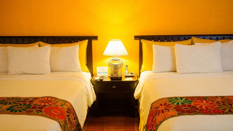 room at clarion copan hotel guatemala with two beds and a nightstand with a lamp in between them