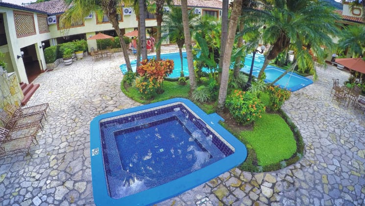 pool area of the clarion copan hotel in guatemala with a separate hot tub and green foliage throughout it
