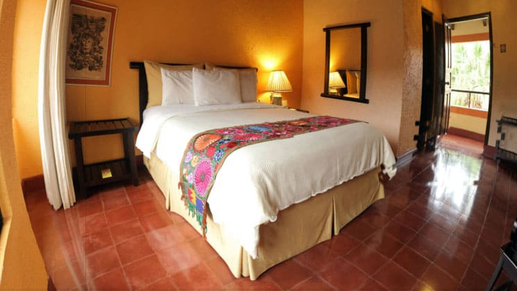 room at clarion copan hotel guatemala with a king bed, tile floors and a mirror on the wall