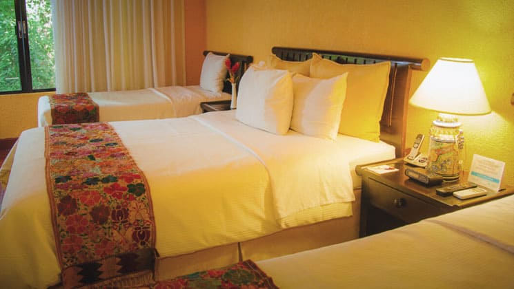 room at clarion copan hotel guatemala with three beds with white linens lined up and a dim light illuminating them
