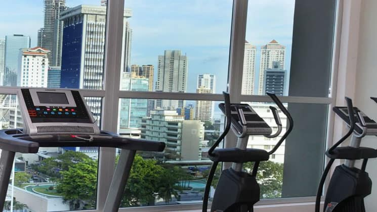 gym room of the clarion victoria panama hotel with treadmills in front of large windows looking out at the city's skyscrapers