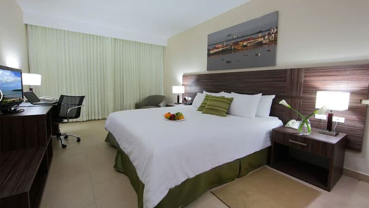 room with a king bed with green accents and a picture on the wall at the clarion victoria panama hotel
