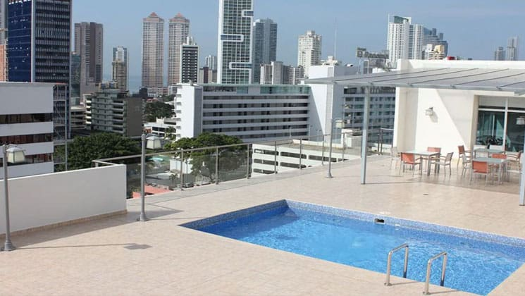 pool area on the roof of the clarion victoria panama hotel with skyscrapers all around it