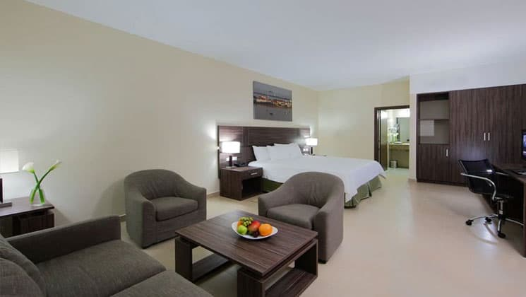 suite room at the clarion victoria panama hotel with a large bed, table and chairs and entry into a bathroom on the far side
