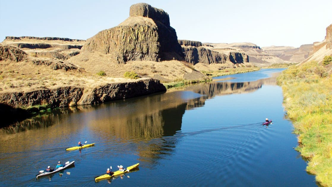 Columbia & Snake Rivers Journey small ship cruise passengers kayaking on calm waters in a sunny pacific northwest gorge