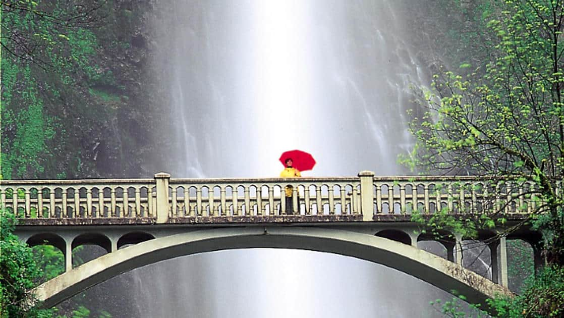 a lone traveler with a yellow jacket and red umbrella stands on the multnomah falls bridge with the waterfall in the background