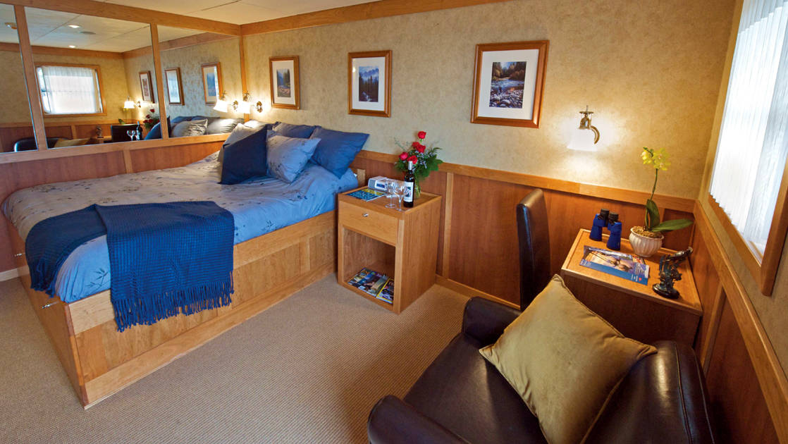 Safari Explorer Hawaii small ship Commander cabin with bed, pictures on the wall and comfortable chair in front of it
