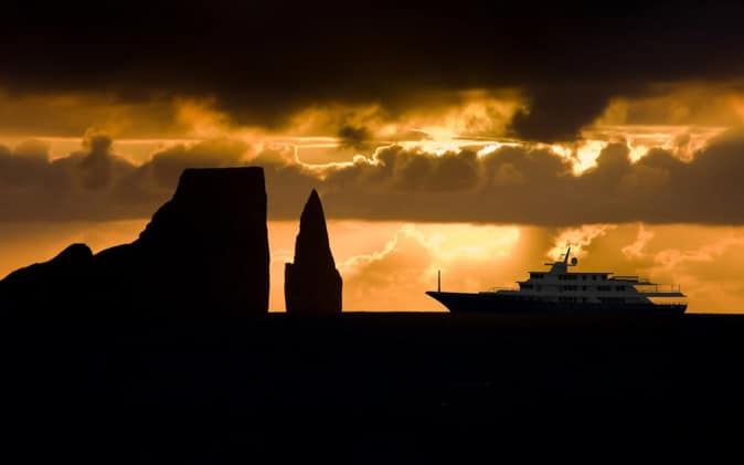 Conservation ship silhouette with sunset skies of orange and kicker rock.