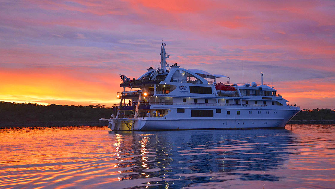 Coral Adventurer cruising away into the sunset in Australia.